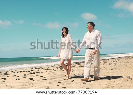 couple walking and laughing along the beach