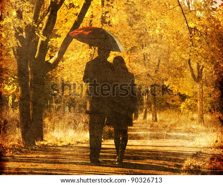 Couple walking at alley in autumn park. Photo in old image style.