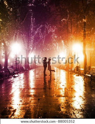 Couple walking at alley in night lights. Photo in vintage multicolor style.