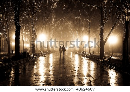 Couple walking at alley in night lights. Photo in vintage yellow style.