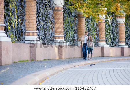 Couple walking by the beautiful grill of Mikhailovsky (Michael) garden of Saint-Petersburg
