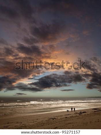 Couple walking dog on beach at sunset