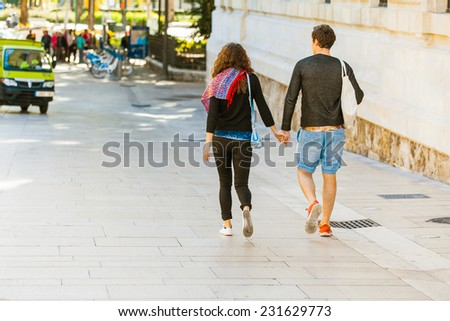 Couple walking hand in hand along Malaga city center. Spain. #231629773