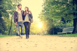 Couple walking hand in hand in a park - Romantic date outdoors