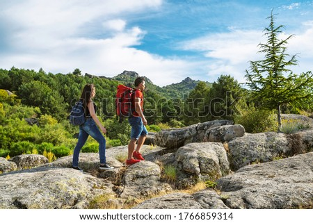 Couple walking in front of each other up the mountain