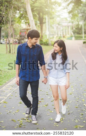 Couple walking in garden. Them hand in hand and smile with happiness.