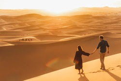 Couple walking in Sahara desert at sunset. View from behind, nature background. Travel, freedom and wanderlust concept.