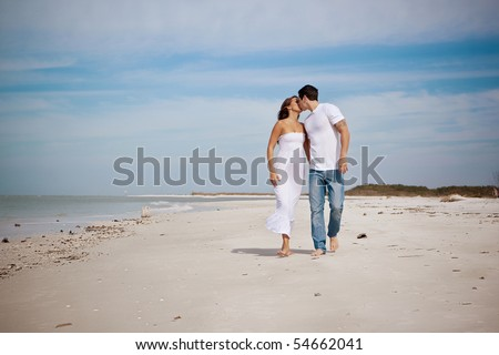 Couple walking on a beach, kissing