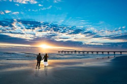 Couple walking on beach at sunrise, enjoying time together. Beautiful cloudy sky over pier and sun reflected on the beach. People relaxing on summer  vacation. Jacksonville, Florida, USA.