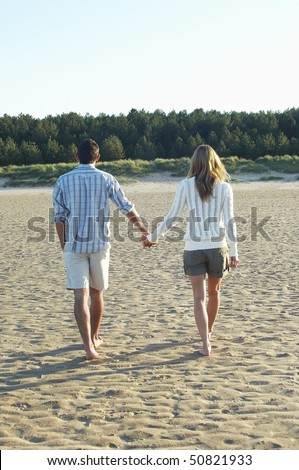 Couple Walking on Beach holding hands, back view