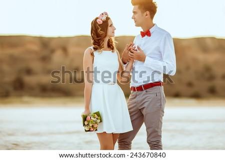 Couple walking on beach. Wedding