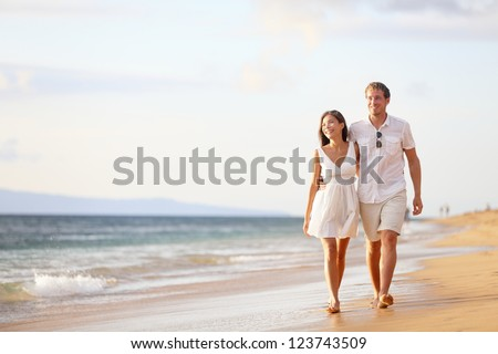 Couple walking on beach. Young happy interracial couple walking on beach smiling holding around each other. Asian woman, Caucasian man.