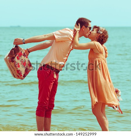 Couple walking on beach. Young happy married hipsters in trendy clothes kissing on beach and holding their shoes. Sunny summer day. Vintage style. Outdoor shot