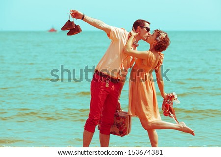 Couple walking on beach Young happy married hipsters in trendy clothes kissing on beach and holding their shoes Sunny summer day Copy-space Outdoor shot