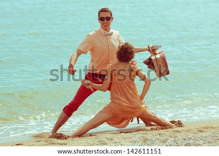 Couple walking on beach. Young happy married hipsters in trendy clothes playing and laughing on beach and holding their shoes and vintage suitcase. Sunny summer day. Outdoor shot