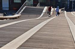 Couple walking on broad walk in waterfront, Spadina WaveDeck, Toronto.