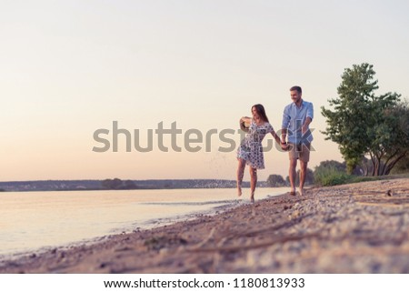 Couple walking on the beach at sunset. Sunset. #1180813933