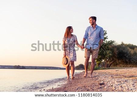 Couple walking on the beach at sunset. Sunset. #1180814035