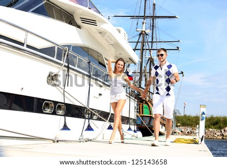 couple walking on the pier at the front of the yachts