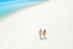 Couple walking on white sand beach in summer, bird eye view - tourist and vocation concepts