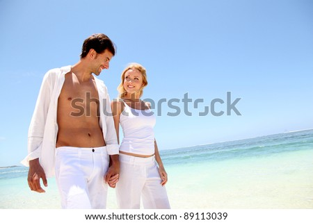 Couple walking on white sandy beach