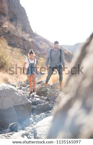 Couple walking over a rocky path in the desert, they are negotiating their steps on the path