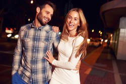 Couple walking through town together at night