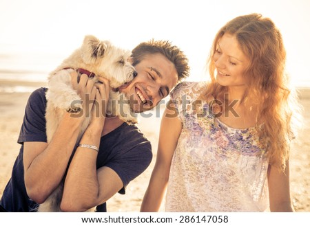 couple walking with dog outdoor. man holding up the cute dog while he licks his face