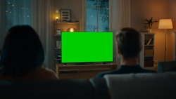 Couple Watches Green Mock-up Screen TV while Sitting on a Couch in the Living Room. Romantic Evening for Boyfriend and Girlfriend.