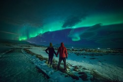Couple watches the northern lights. Woman and man at winter night landscape . Iceland.