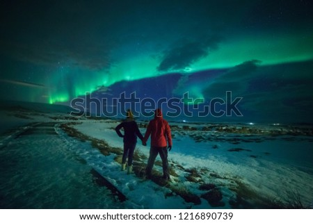 Couple watches the northern lights. Woman and man at winter night landscape . Iceland. #1216890739