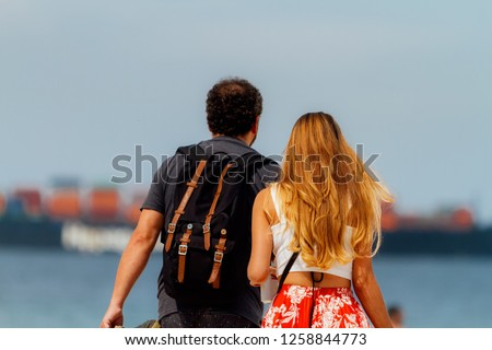 Couple watches the passing of a freighter from the Copacabana beach in Rio de Janeiro (Brazil)
