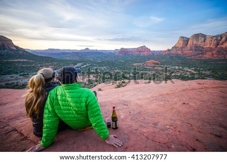 Couple watching a desert sunset with a bottle of wine in Sedona, AZ.