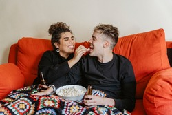 couple watching a film on the sofa eating popcorn laughing