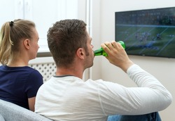 Couple watching American football on tv.