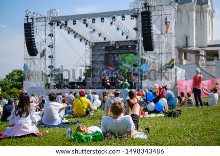 Couple watching concert at open air music festival, back view, stage and spectators at background