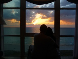 Couple watching the sunrise through a window overlooking the Atlantic Ocean in Miami Beach, Florida, spring 2011