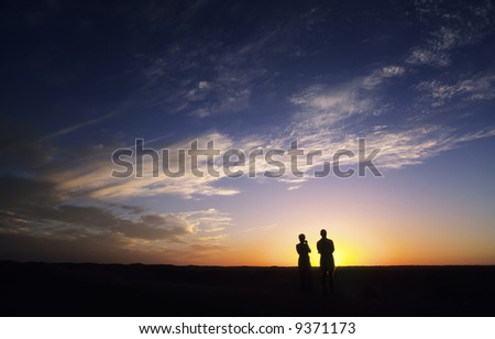 Couple watching the sunset; sahara desert, Algeria, Africa.