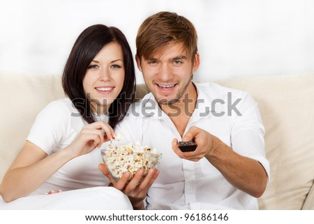 Couple watching tv in their living room at home, young happy smile man and woman eat popcorn, sitting on couch, sofa, hold remote control