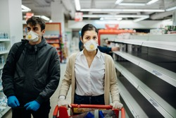 Couple wearing masks and gloves buying groceries/supplies in supermarket with sold out products.Food supplies shortage.Empty shelves due to coronavirus covid-19 outbreak panic buying and hoarding.