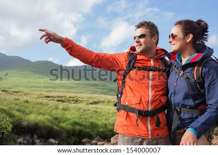 Couple wearing rain jackets and sunglasses admiring the scenery with man pointing in the countryside