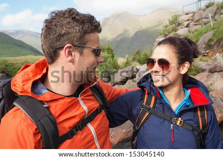 Couple wearing rain jackets and sunglasses smiling at each other in the countryside