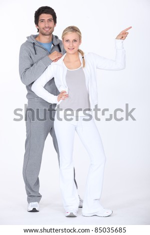 Couple wearing tracksuits pointing off camera