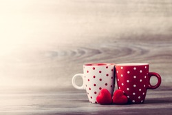 Couple white and red cups with decoration by red hearts on wooden table. Valentines day celebration concept. Copy space.