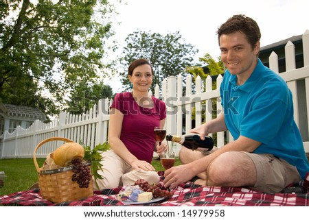 Couple with a picnic spread with wine, cheese and bread.  They are smiling and facing the camera. Horizontally framed shot.