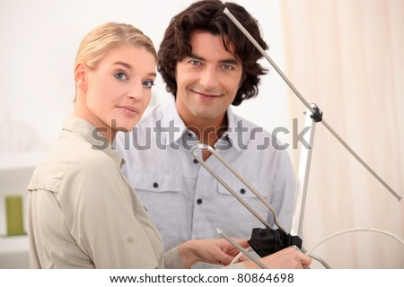Couple with a television antenna - stock photo
