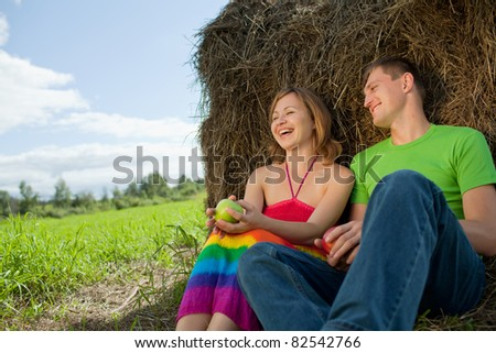 couple with apples sitting on the grass