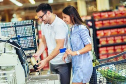 Couple with bank card buying food at grocery store or supermarket self-checkout