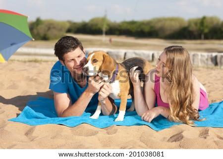 Couple with beagle on the beach