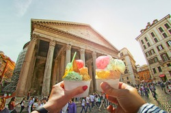 Couple with beautiful bright  sweet Italian ice-cream with different flavors  in the hands   on background of Pantheon , Italy
